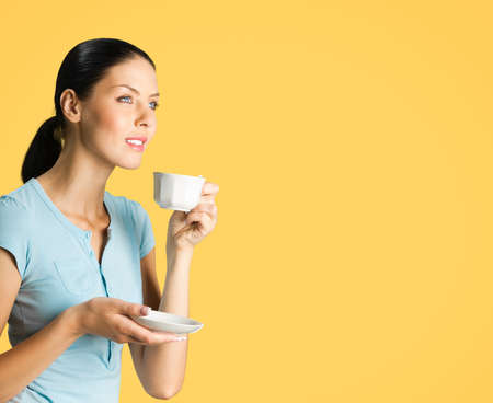 Portrait of young smiling brunette woman drinking coffee, looking forward, isolated over orange yellow color background. Copy space blank area for some text.