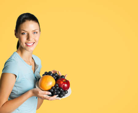 Portrait image of young happy smiling attractive woman in blue casual smart clothing, with plate of fruits, posing at studio against orange yellow background, with copy space blank area for text.