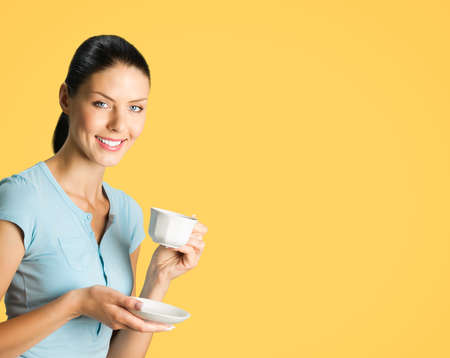 Portrait of young smiling brunette woman drinking coffee, isolated over orange yellow color background. Copy space blank area for some text or slogan.