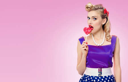 Woman eating heart shape lollipop dressed in pinup style dress in polka dot, over pink background. Caucasian blond model posing in retro fashion and vintage studio concept. Standard-Bild