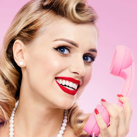Woman with phone, in pin up style dress, showing blank signboard with copyspace area, on pink background. Blond model posing in retro fashion and vintage studio concept. Square.