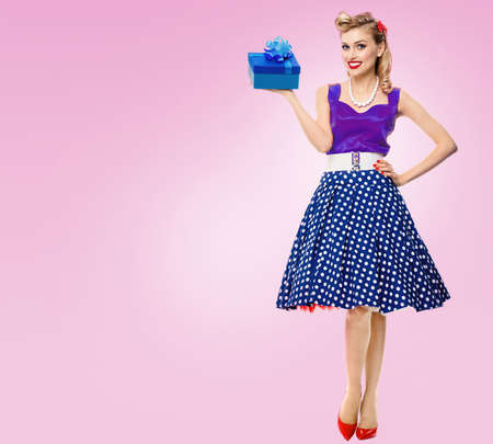Smiling woman dressed in pin up style dress with polka dot, on pink background. Caucasian model posing in retro fashion and vintage concept studio concept. Standard-Bild
