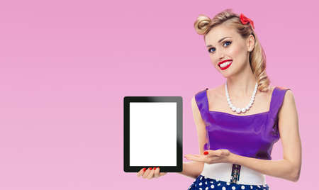 Woman showing blank tablet pc monitor, with copy space, dressed in pin up style dress in polka dot, pink background. Blond model posing in retro fashion vintage concept.
