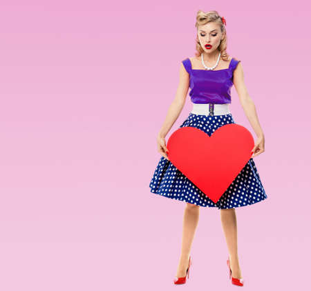 Woman holding heart symbol, dressed in pin up style dress with polka dot, on pink background. Caucasian blond model posing in retro fashion and vintage studio concept.