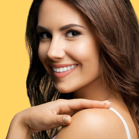 Portrait of smiling beautiful woman in white casual tank top looking at camera, over yellow color background. Brunette girl at studio concept.