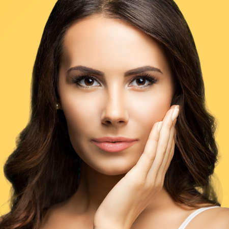 Portrait of beautiful woman in white casual tank top, over yellow color background. Brunette lovely girl at studio fashion concept. Square composition image. Standard-Bild