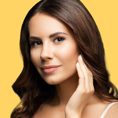 Portrait of beautiful woman in white casual tank top, over yellow color background. Brunette girl at studio beauty concept. Square composition image.
