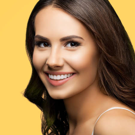 Portrait of smiling beautiful woman in white casual tank top looking at camera, over yellow color background. Brunette girl at studio concept. Square composition.