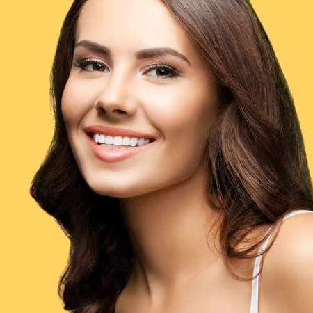 Portrait of smiling beautiful woman in white casual tank top, over yellow color background. Brunette girl at studio concept. Square composition.