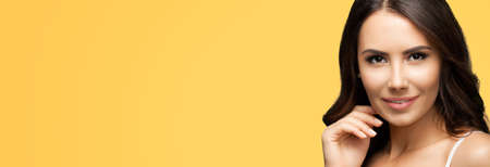 Portrait of smiling beautiful woman in white casual tank top, over yellow color background. Brunette girl at studio beauty fashion concept. Wide horizontal banner composition.
