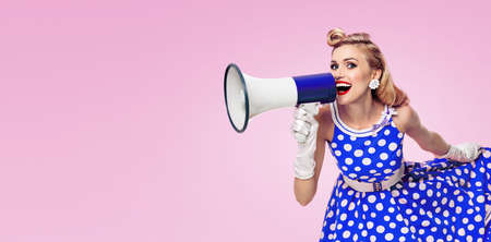 Image of woman holding megaphone, dressed in pin up style blue dress in polka dot white gloves, over pink colour background. Female blond model posing in retro fashion vintage studio concept.