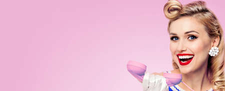 Image of beautiful happy excited woman with phone, isolated over pink background. Caucasian blond pinup girl posing in retro studio concept. Wide.