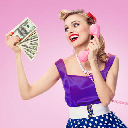 Image of happy woman with money, talking on phone, pin-up style dress in polka dot, over pink background. Caucasian blond model posing in retro fashion and vintage studio shoot.