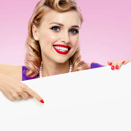 Image of smiling blond woman in pin up style dress, showing blank signboard with copyspace, over pink background. Blond model posing in retro fashion and vintage studio concept. Square. Standard-Bild