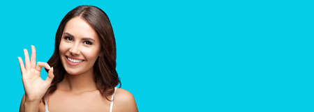 Photo of woman showing ok okay hand sign or zero gesture, isolated on aqua blue green color background. Portrait of happy smiling gesturing brunette girl at studio. Wide horizontal banner composition.