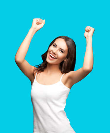 Photo of happy gesturing beautiful woman rising hands up with clenching fists, in white smart casual clothing, isolated over aqua blue green color background. Excited brunette girl at studio.