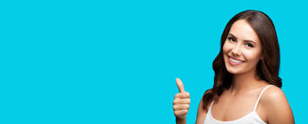 Photo of woman showing thumb up hand sign or like gesture, isolated on aqua blue green color background. Portrait of happy smiling gesturing brunette girl at studio. Wide horizontal banner composition