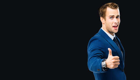 Photo of excited businessman showing thumbs up like hand sign gesture, in blue confident suit, standing over black color background. Handsome happy man at studio. Copy space for some slogan or text.