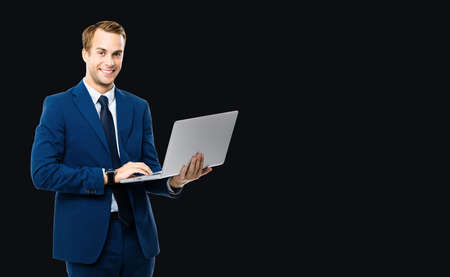Photo of happy smiling businessman working with laptop, isolated over black color background. Business man in blue confident suit and tie, with notebook in studio concept. Standard-Bild