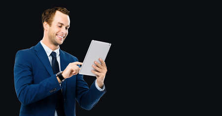Photo of smiling businessman using touchpad tablet pc, isolated over black background. Business man in studio concept. Copy space for some text.