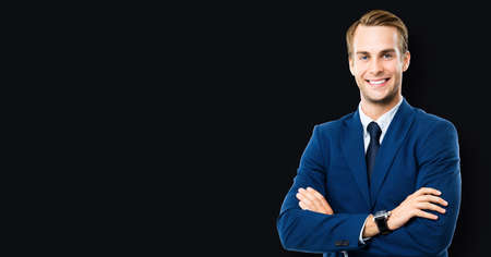 Portrait photo of businessman in blue suit and tie, with crossed arms, standing over black color background. Business success concept. Smiling confident man at studio. Copy space for some text. Standard-Bild