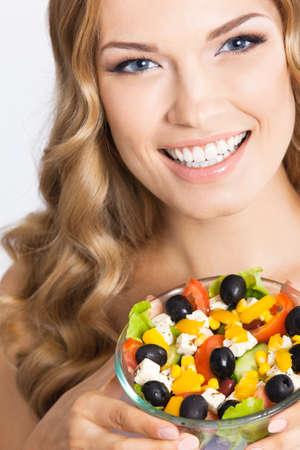Portrait photo of happy smiling beautiful woman with healthy salad, isolated on grey background. Attractive blond girl at studio. Keto ketogenic diet concept.