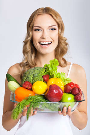 Portrait photo of happy smiling young beautiful woman with healthy vegetarian raw food, over gray background. Attractive blond girl at studio.