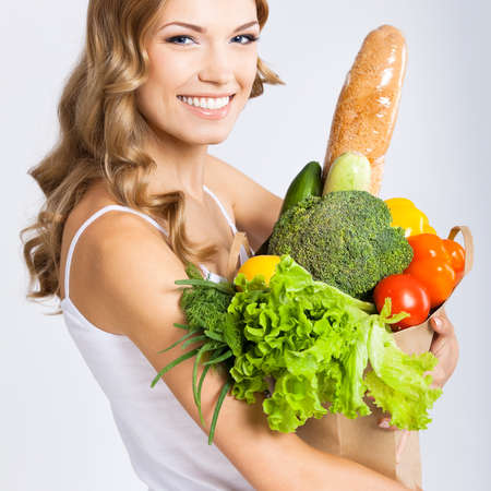 Portrait photo of happy smiling young beautiful woman holding grocery shopping bag with healthy vegetarian raw food, isolated over gray background. Attractive blond girl at studio. Square composition. Standard-Bild