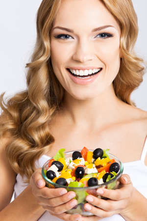 Portrait photo of happy smiling young beautiful woman with healthy salad, isolated over grey background. Attractive blond girl at studio. Keto ketogenic diet concept.