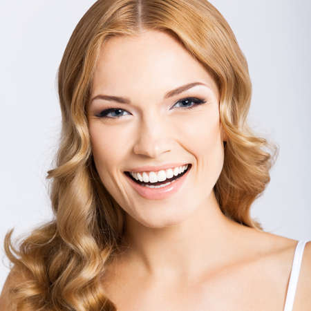 Face portrait photo of beautiful young cheerful smiling woman, over gray background. Happy amased attractive blond girl at studio. Dental health concept.