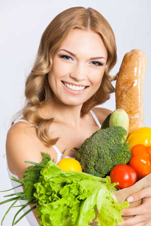 Portrait photo of happy smiling young beautiful woman holding grocery shopping bag with healthy vegetarian raw food, isolated on gray background. Attractive blond girl at studio.