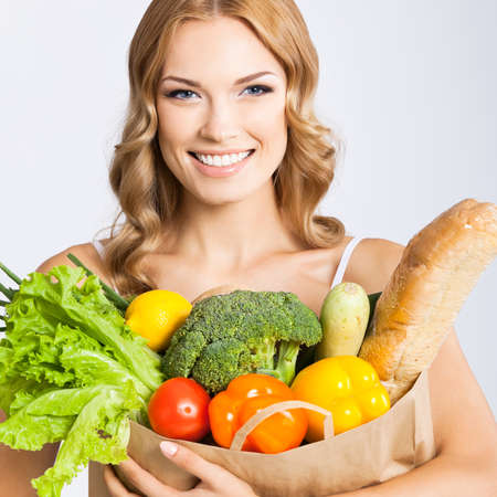 Portrait photo of happy smiling young beautiful woman holding grocery shopping bag with healthy vegetarian raw food, isolated over gray background. Attractive blond girl at studio. Standard-Bild