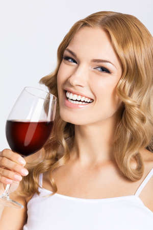 Studio photo of happy smiling woman with glass of red wine, isolated over gray background. Attractive blond girl drinking redwine.