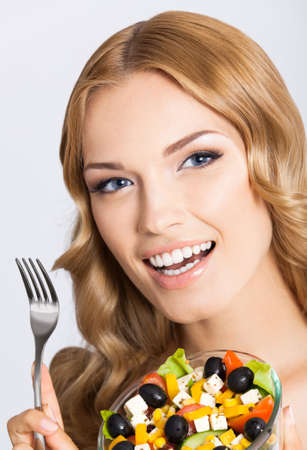 Photo of happy smiling beautiful woman with healthy salad, grey background. Attractive blond girl at studio. Keto ketogenic diet concept.