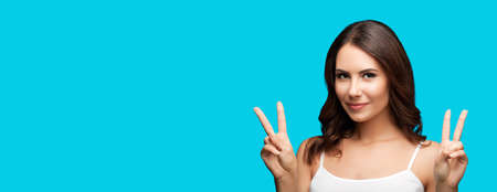 Photo of woman showing two fingers or victory hand sign gesture, isolated on aqua blue green color background. Portrait of happy smiling gesturing brunette girl at studio. Wide banner composition.