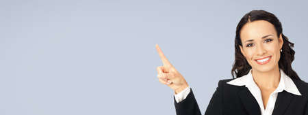 Photo image of happy smiling woman in black confident suit, showing pointing at copy space. Business concept. Isolated over grey background. Brunette businesswoman. Wide. Standard-Bild