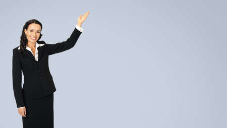 Photo image of happy smiling attractive woman in black confident suit, showing copy space. Business concept. Isolated over grey background. Brunette businesswoman. Standard-Bild