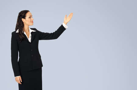 Photo image of happy smiling woman in black confident suit, showing at copy space. Business concept. Isolated over grey background. Brunette businesswoman.