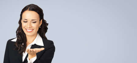 Photo image of happy smiling beautiful business woman showing something or copyspase for product, looking at hand, isolated over grey color background. Wide composition.