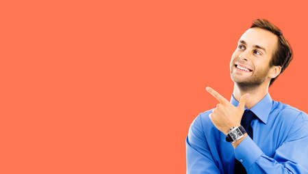 Portrait of confident businessman looking aside, pointing showing something, isolated over bright vivid orange color background. Mock up copy space free area. Happy smiling business man at studio.