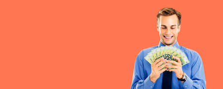 Portrait of smiling businessman holding and looking at money, euro cash banknotes over bright vivid orange color background. Confident happy man at studio. Copy space for text. Wide banner composition