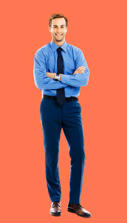 Full length body portrait of happy smiling businessman in blue cloth, standing in crossed arm pose, isolated over bright vivid orange color background. Confident business man at studio image.