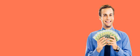 Portrait of smiling businessman holding money, euro cash banknotes, isolated over bright vivid orange color background. Confident happy man at studio. Copy space for some text. Wide banner composition.