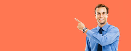 Photo of confident businessman pointing showing something, isolated over bright vivid orange background. Mock up copy space free area. Success in business and education concept.