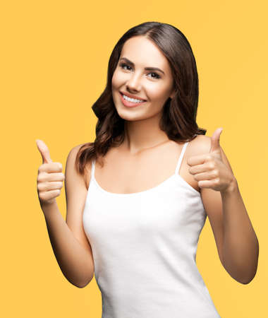 Photo of woman showing thumbs up hand sign or like gesture, isolated on orange yellow color background. Portrait of happy smiling gesturing brunette girl at studio.