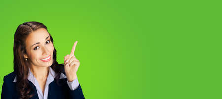Photo of young happy smiling woman in black confident suit, showing pointing at mock up copy space for text. Business ad concept. Green color background. Wide horizontal image.