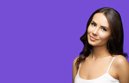 Portrait of happy smiling beautiful woman in white casual tank top, on violet purple background. Brunette lovely girl at studio beauty fashion concept. Wide horizontal composition image.