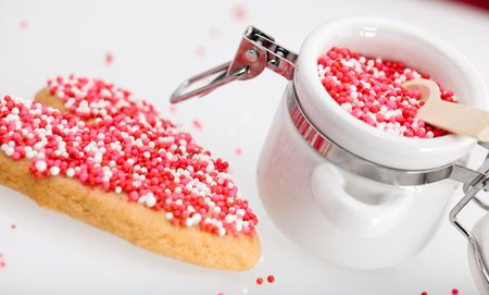 indulging: Red, white and pink nonpareils on heart-shaped cookie and in white porcelin storage jar.