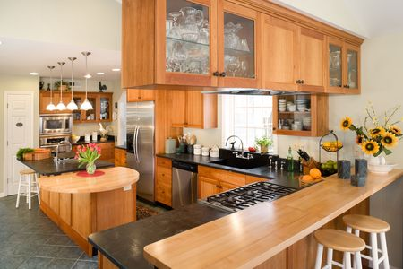 home appliances: Modern gourmet kitchen featuring cherry cabinets and black soapstone.