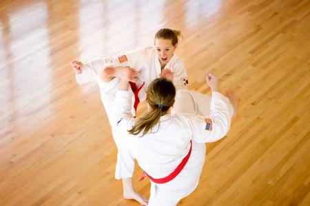 spar: Two teenage girls wearing red belts spar with high kicks.